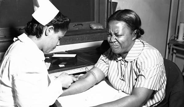 Woman grimacing while having blood drawn.