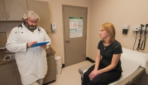 A doctor consults a patient's electronic health record on a tablet device.